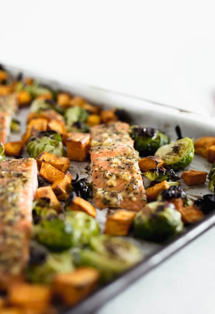 Closeup of a filet of Maple Dijon Salmon with Brussels Sprouts and Sweet Potatoes on a sheet pan.