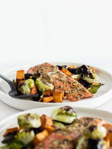Filet of maple dijon salmon with brussels sprouts and sweet potatoes on a white plate with a black fork.