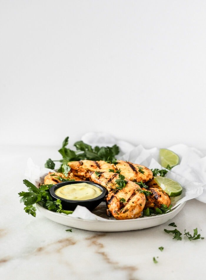 Thai Coconut Grilled Chicken Tenders on a plate With a small bowl of Coconut Turmeric Dipping Sauce surrounded by cilantro and limes.