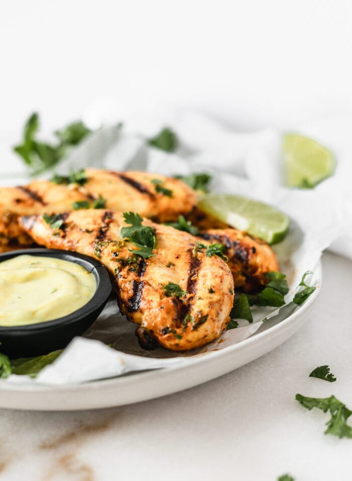 closeup of Thai Coconut grilled Chicken Tenders on on a plate with coconut turmeric dipping sauce.