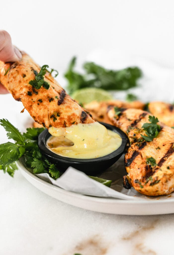 coconut grilled chicken tender being dipped into a small bowl of coconut turmeric dipping sauce.