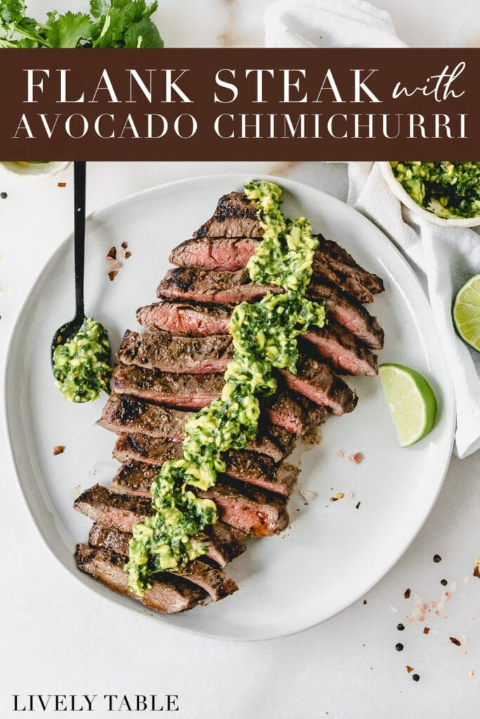 overhead view of sliced grilled flank steak with avocado chimichurri sauce on top on a white plate with a lime wedge and a spoon of sauce with text overlay.