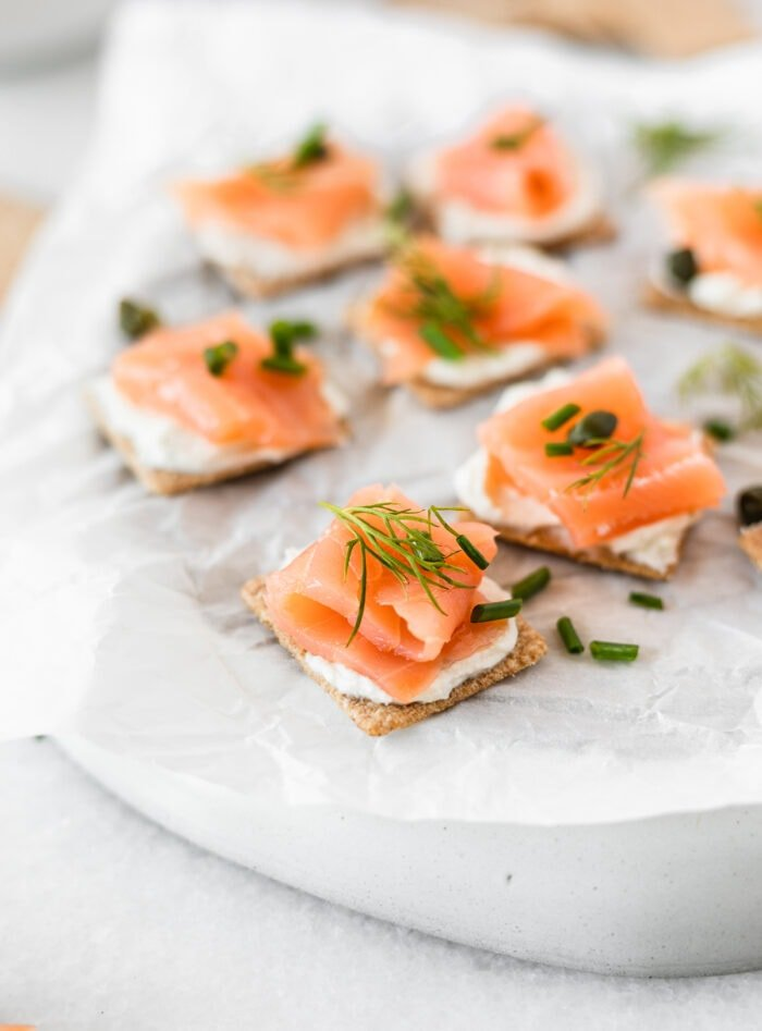 closeup of smoked salmon bites topped with fresh herbs on a white parchment covered plate.