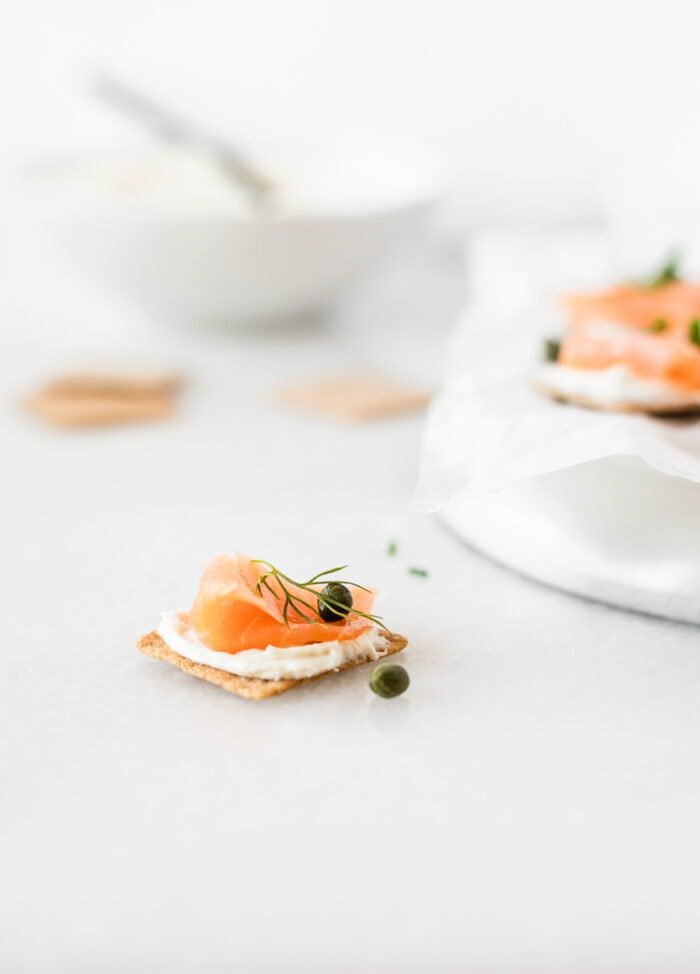 smoked salmon bite on a cracker with capers on a white backdrop.