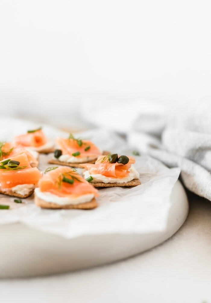 smoked salmon bites topped with fresh herbs and capers on a white parchment covered plate.