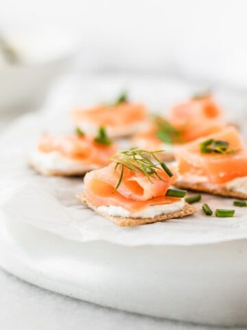 Close up of smoked salmon bites topped with fresh herbs on a white parchment covered plate.