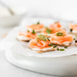 These easy 5 Ingredient Smoked Salmon Bites are easy to make for your next party, and taste amazing! Your guests will love these crackers topped with a flavorful garlic herb spread and smoked salmon. (gluten-free)