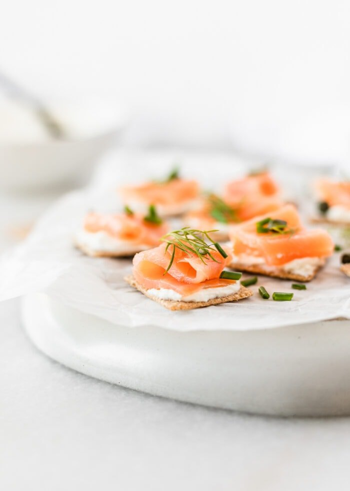 smoked salmon bites topped with fresh herbs on a white parchment covered plate.