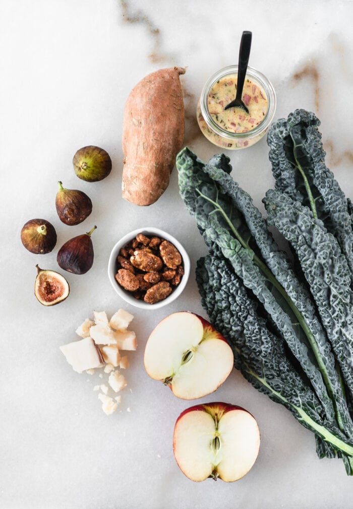 overhead view of ingredients needed to make a warm fall harvest kale salad on a white marble background.