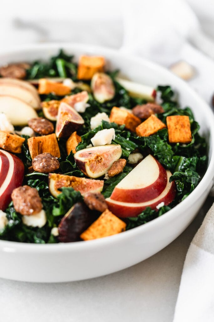 closeup of warm fall harvest kale salad in a white bowl.