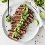 overhead view of sliced grilled flank steak with avocado chimichurri sauce on top on a white plate with a lime wedge and a spoon of sauce.