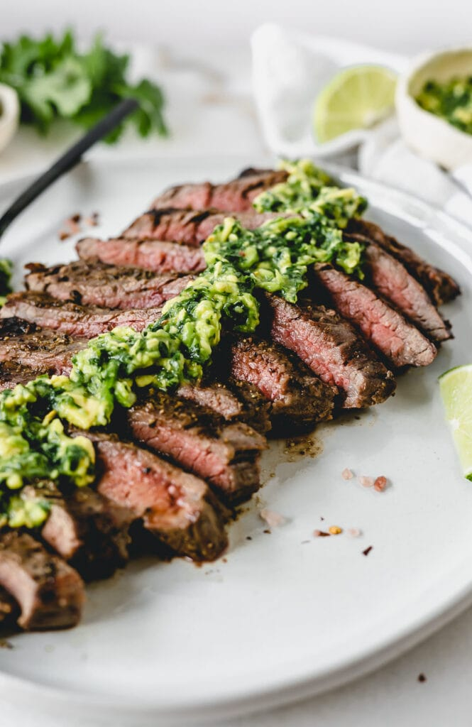 Closeup of sliced grilled flank steak with avocado chimichurri on top.