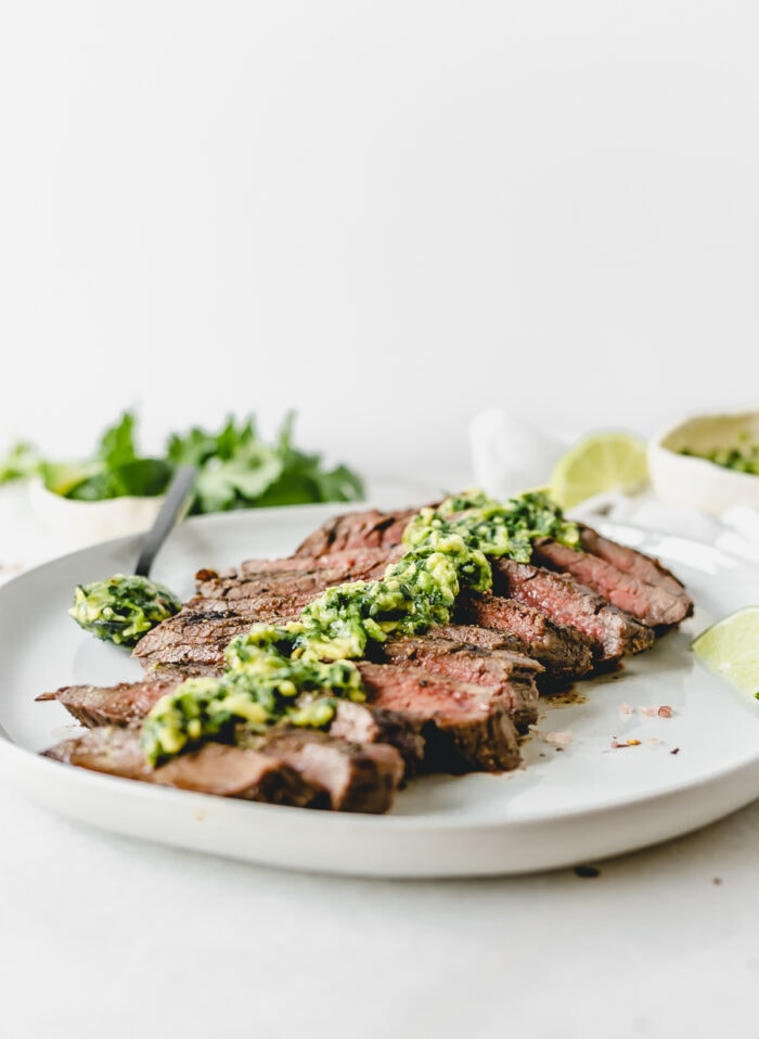 sliced grilled flank steak with avocado chimichurri on top on a white plate with a spoon of avocado chimichurri next to it.