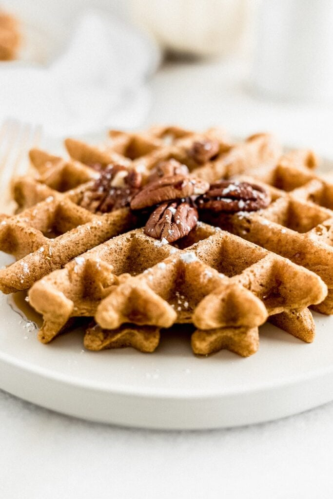 healthy pumpkin waffle on a plate with pecans on top and syrup being poured over it.