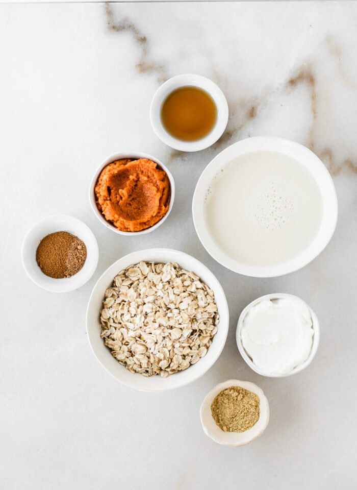 overhead view of ingredients needed to make pumpkin spice overnight oats on a white marble background.