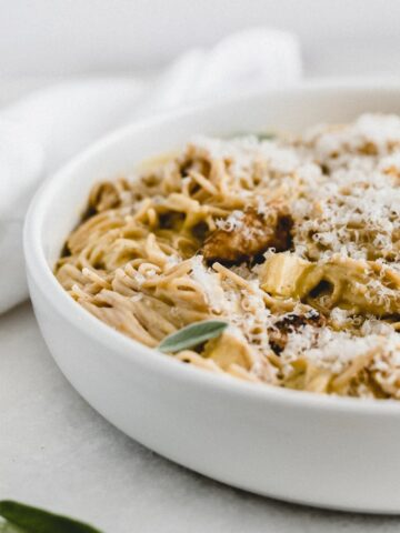 closeup of butternut squash sage chicken spaghetti covered with parmesan cheese in a white bowl.