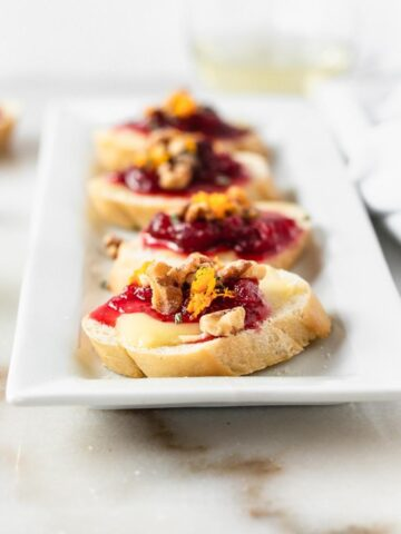 Close up of cranberry brie crostini topped with toasted walnuts on a white appetizer plate.