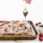raspberry scones getting drizzled by dark chocolate