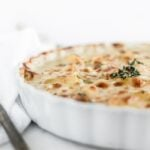 closeup of healthier cheesy scalloped potatoes in a white baking dish with thyme on top.