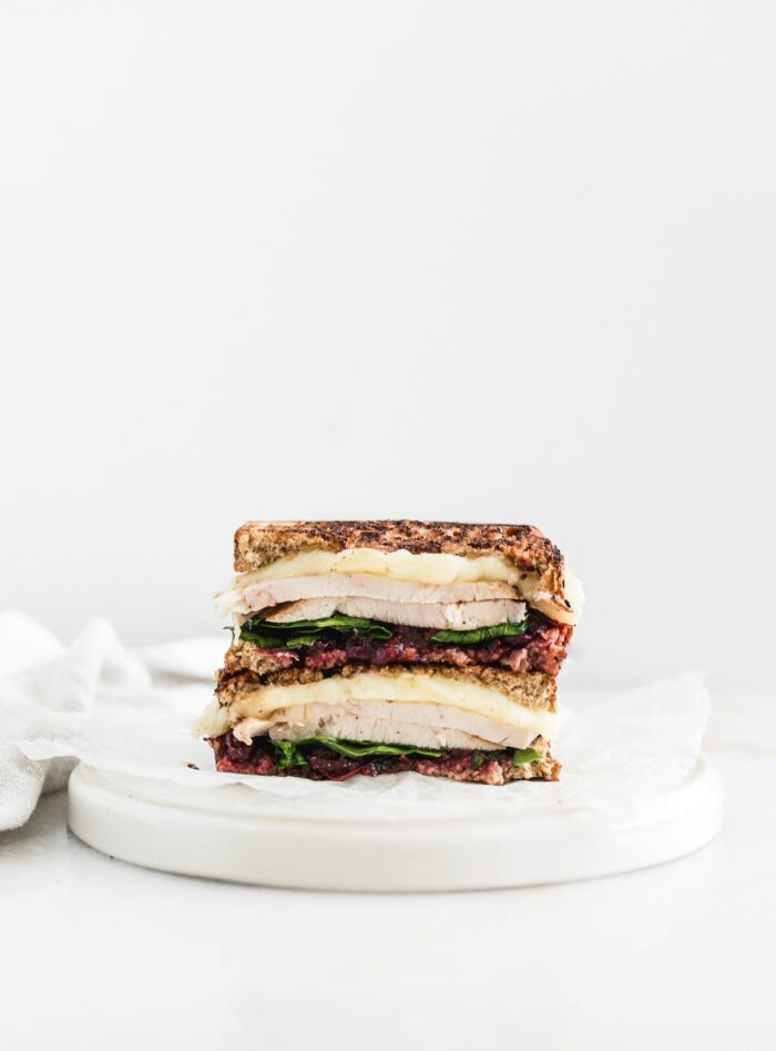 cranberry brie turkey sandwich cut in half and stacked on a white plate.