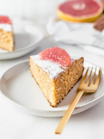 slice of grapefruit olive oil cake with a gold fork on a plate.