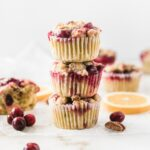 3 cranberry orange streusel muffins stacked on top of each other.