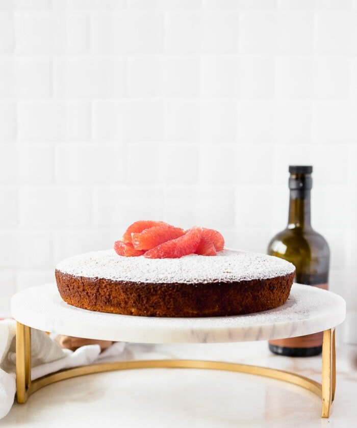 grapefruit olive oil cake topped with powdered sugar and grapefruit segments on a marble and gold stand with a bottle of olive oil in the background.