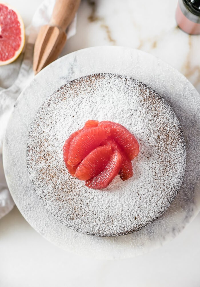 overhead view of grapefruit olive oil cake topped with powdered sugar and grapefruit segments on a white marble stand.