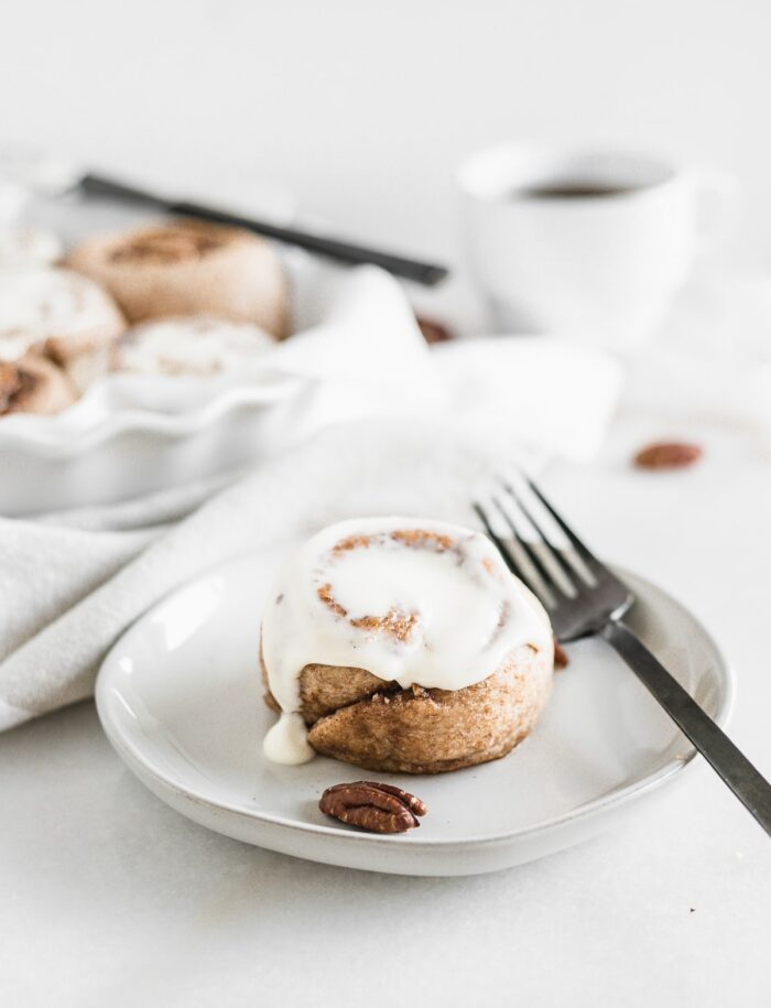 sourdough pecan cinnamon roll on a small grey plate with a black fork next to it.