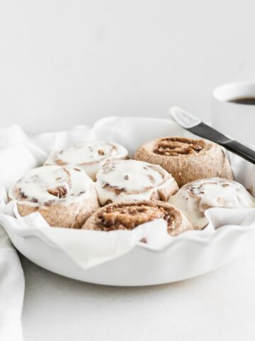cinnamon rolls with frosting in a round white baking dish lined with parmchment.