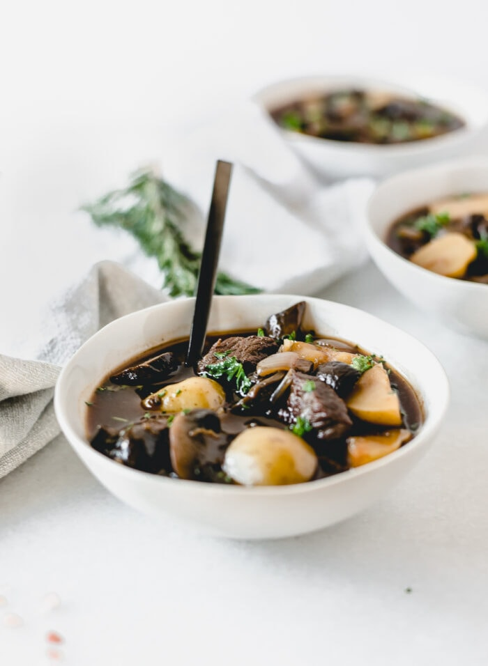 bowl of rosemary mushroom beef stew with a black spoon in it.