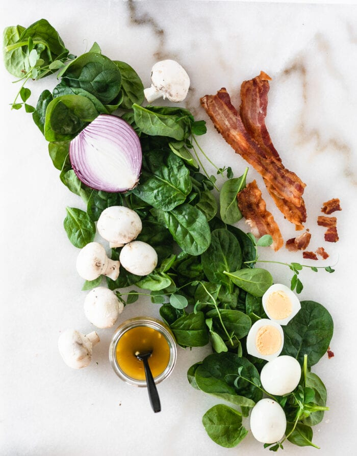 Overhead view of ingredients needed to make spinach salad with warm bacon dressing on a white background.