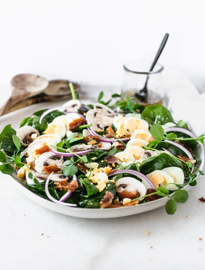 spinach salad on a grey plate topped with sliced mushrooms, boiled eggs, red onion and bacon pieces.