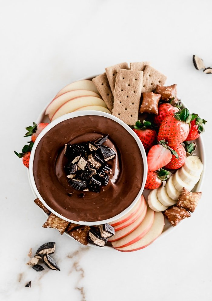 Overhead view of a bowl of Healthy Peanut Butter Cup Cheesecake Dip on a plate with fruit, pretzels and graham crackers.