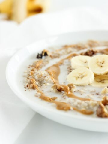 closeup white bowl of steel cut oatmeal topped with peanut butter, bananas, and milk.