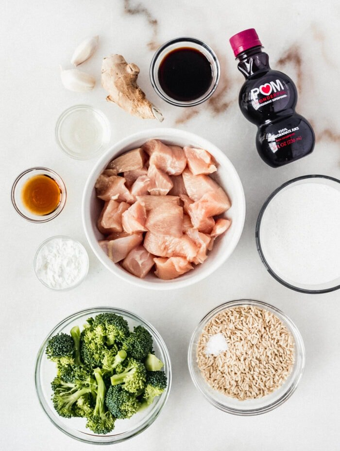 overhead view of ingredients needed to make pomegranate ginger chicken and broccoli on a white backdrop.