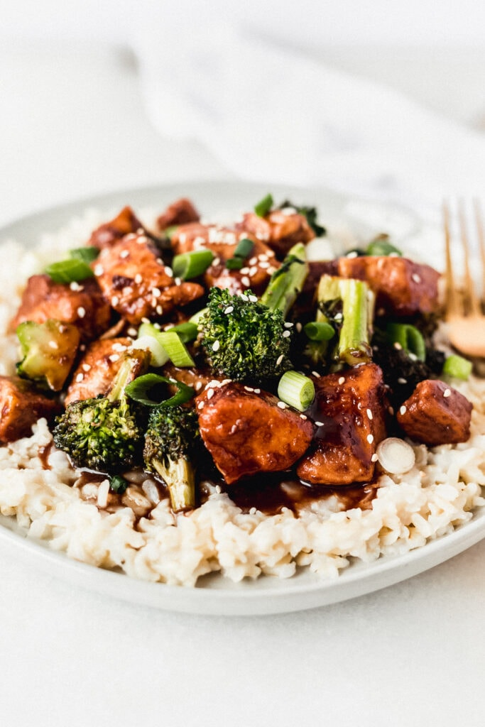 closeup of pomegranate ginger chicken and broccoli on top of coconut brown rice on a plate.