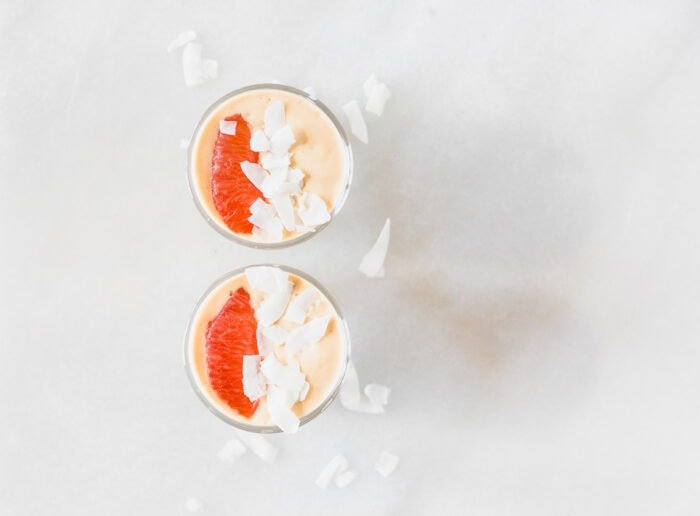 overhead view of two grapefruit smoothies in glasses each topped with a grapefruit slice and coconut flakes.