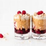 Two glasses with layered PB&J overnight oats with drizzled peanut butter and raspberries on top.