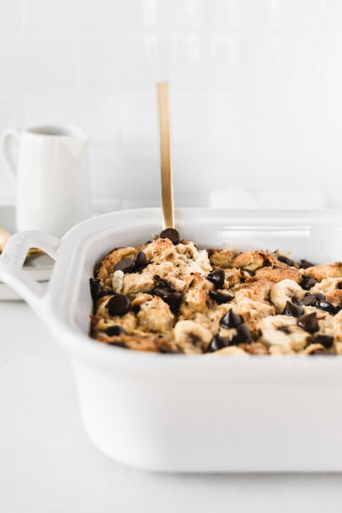 closeup of bourbon banana chocolate chip bread pudding in a white baking dish with a gold serving spoon in it.