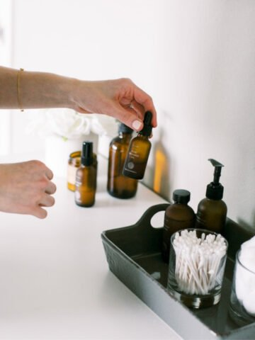 hand picking up an amber glass bottle of a serum from a vanity tray.