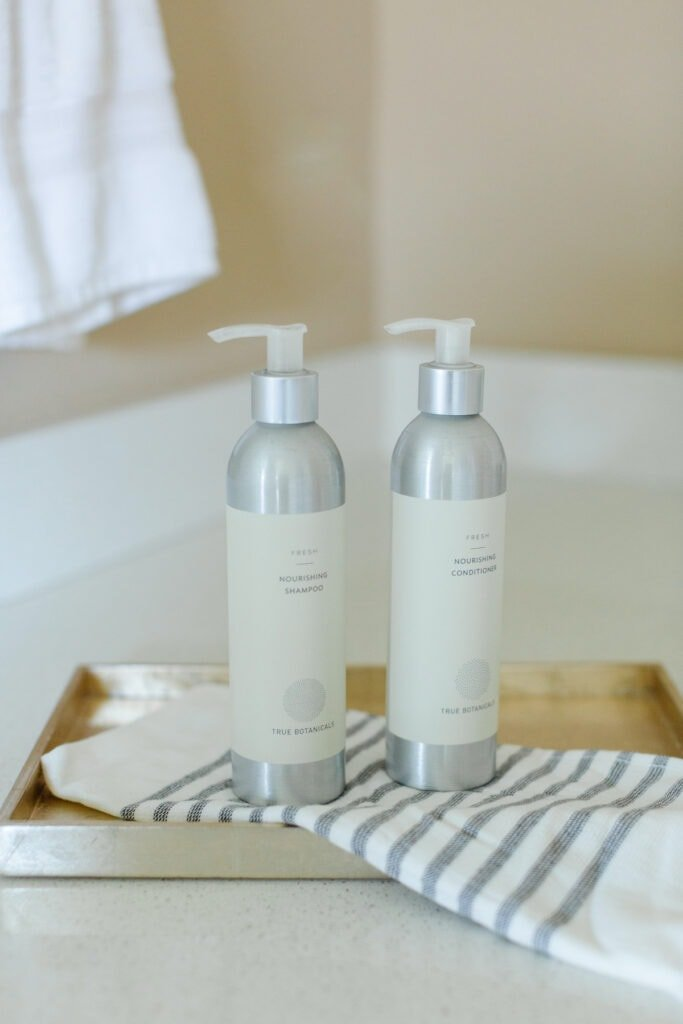 shampoo and conditioner bottles on a tray with a striped towel.