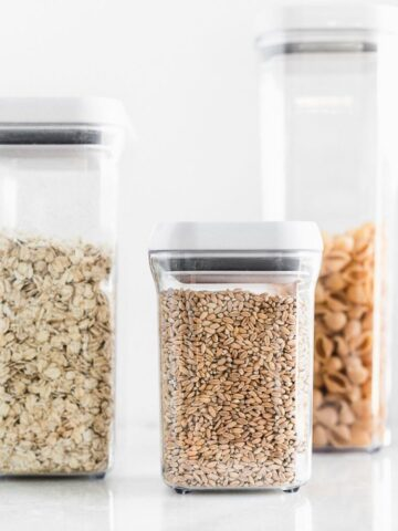 whole grains in clear 3 plastic containers with white lids.
