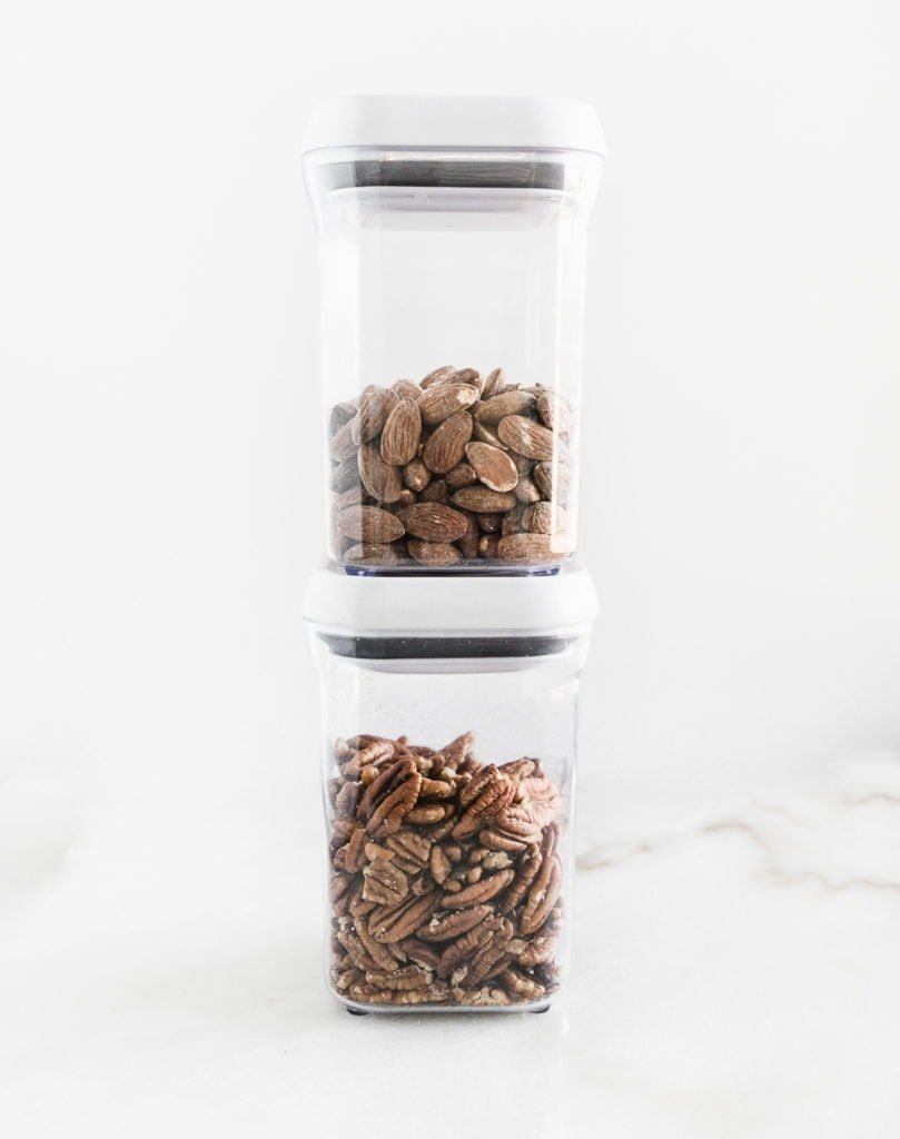 two clear plastic canisters with nuts in them stacked on top of each other.