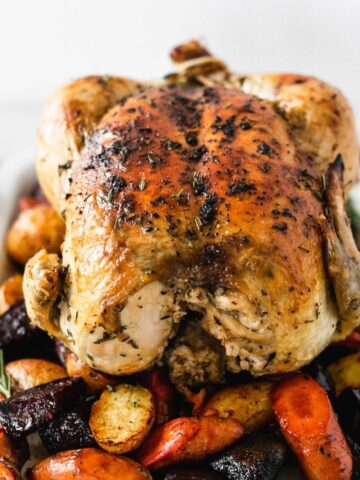 perfect whole roasted chicken with root vegetables in a cast iron skillet