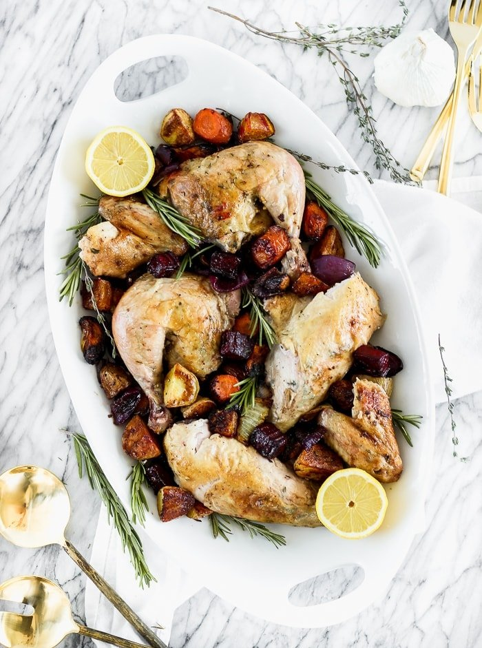 perfect whole roasted chicken with root vegetables cut up on a platter