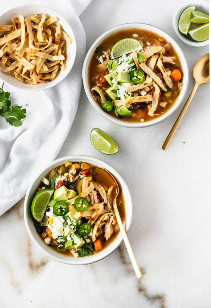 overhead view of two bowls of chicken tortilla soup topped with tortilla strips, jalapeno slices, avocado and limes with gold spoons and a bowl of tortilla strips.
