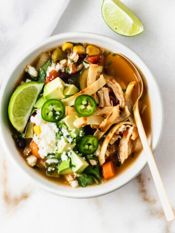bowl of chicken tortilla soup with avocado, limes, and tortilla strips on top.