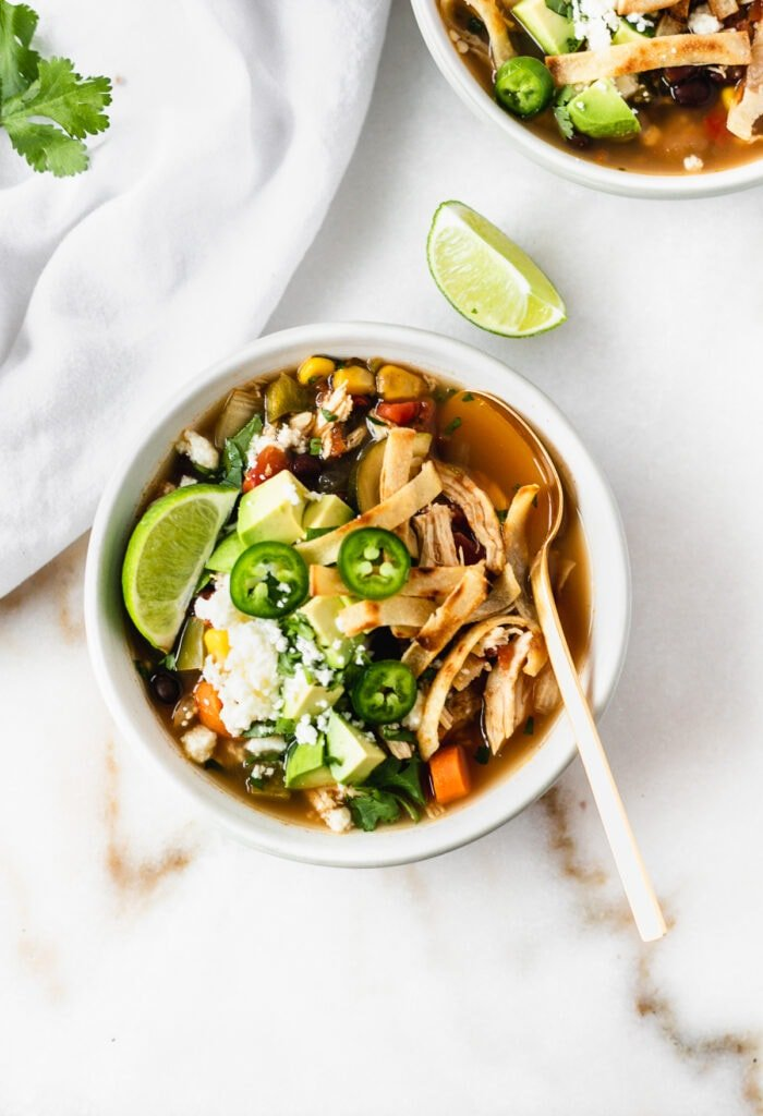 overhead view of a bowl of chicken tortilla soup topped with avocado, jalapeno and tortilla strips.