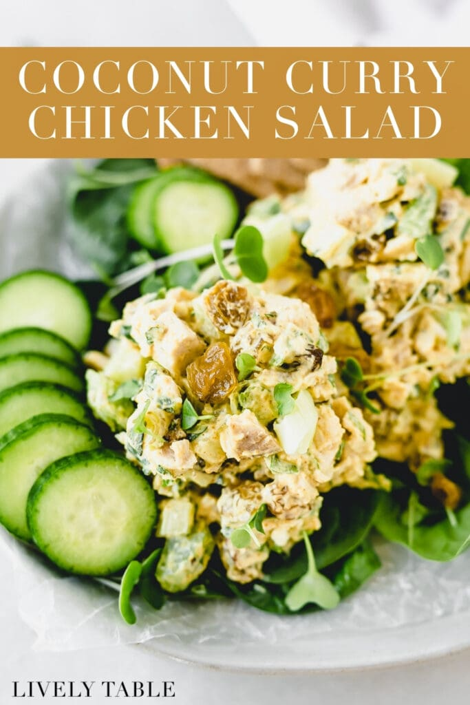 coconut curry chicken salad and sliced cucumbers on top of greens on a plate with text overlay.